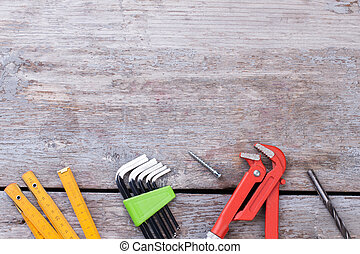 Various tools for construction on wooden background.