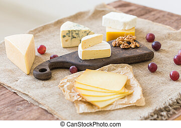 Various types of cheese, blue cheese and brie with grapes and nuts.