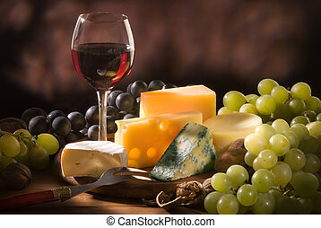 Glass of red wine with various types of cheese and garnishes