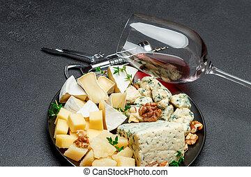 various types of cheese in dark plate