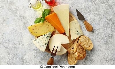 Various types of cheese served on rustic wooden board. ...