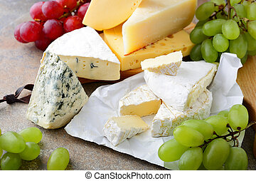 Various types of Cheese with grapes on slate