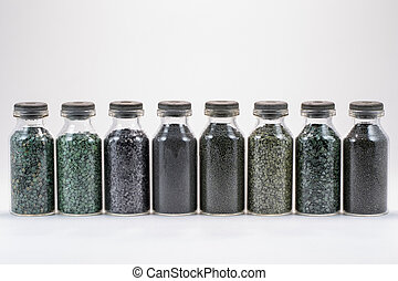 Various types of gunpowder in glass jars on a white background