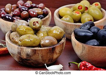 Various types of olives in a wooden bowls