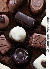 Various types of pralines isolated on chocolate background