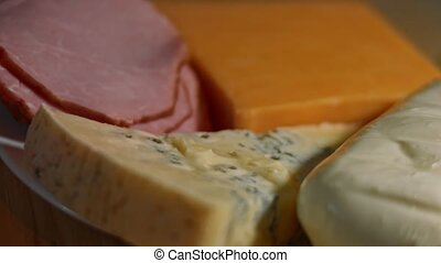 Various types of savory and fresh cheeses and pork ham ready to be cut as appetizer, 4K video. Slowmotion