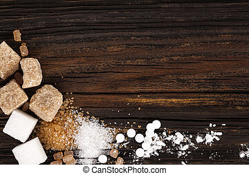 Various types of sugar - brown sugar, white sugar, crystal sugar, artificial sweetener, cane sugar and powdered sugar from above on wooden table