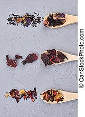 Various types of tea leaves in wooden spoons.