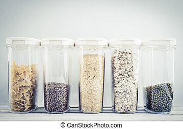 Various uncooked cereals, grains, beans and pasta for healthy cooking in plastic containers on wooden table, blue background, close-up. Food storage concept