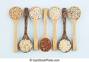 Various varieties of rice and wholegrains in spoon on wooden table background. Wheat, barley, millet, oats, rice, coarse grain, sorghum, lotus seed.