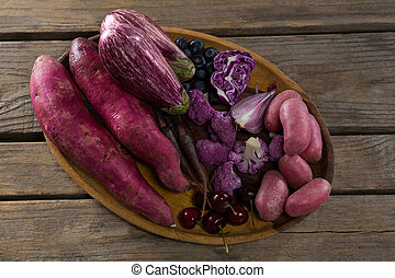 Various vegetables in a tray on wooden table