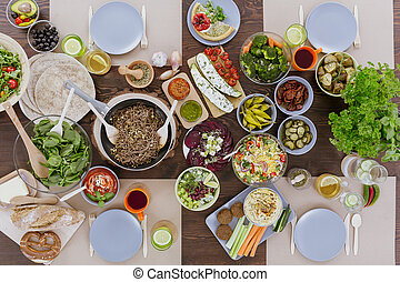 Various colorful vegetarian dishes lying on wooden table