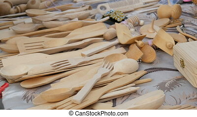 Various wooden spoons and forks at the fair. Wooden kitchen appliances on the market counter.