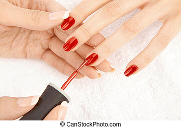 The female hand puts a varnish on nails of the female fingers, isolated