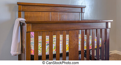 Varnished wooden crib inside a nursery