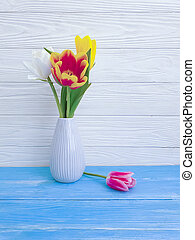 vase bouquet of tulips on wooden background