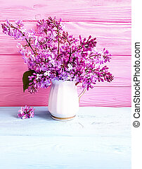 vase of lilac bouquet on wooden background
