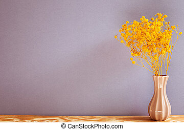 Vase of yellow baby's breath gypsophila dry flowers on wooden table with purple background