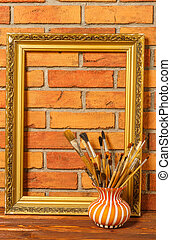 Vase with artistic brushes and the frame on the background of ol
