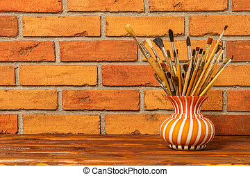 Vase with artistic brushes on the background of old red brick wa