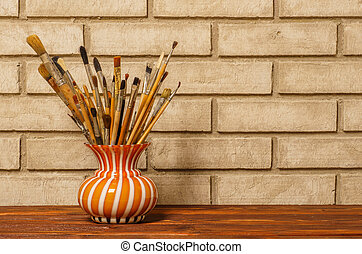 Vase with artistic brushes on the background of old white brick