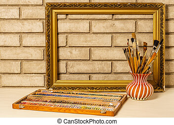 Vase with artistic brushes, pastels and the frame on the backgro