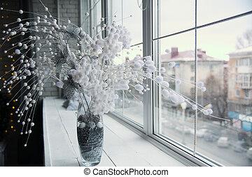 Vase with flower arrangement on the windowsill.