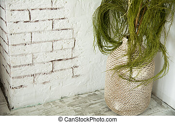 Vase with green branches on the floor