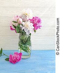 vase with peony flower on wooden background