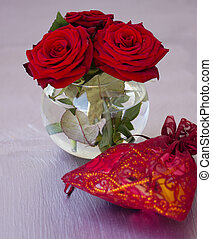 vase with red roses on the table