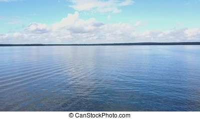 Vast blue lake background with moderate waves looking...