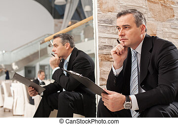 vasthouden, middelbare leeftijd , fris, kin, nadenkend, zittende , man, zoeken, formalwear, trap, hand, kijken weg, ideas., terwijl