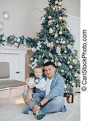 vater sohn, mit, von, a, weihnachtsbeleuchtung, und, dekorationen, in, der, hintergrund., neujahrs, szenerie