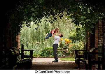 vater tochter, in, sommer, kleingarten, in, pflanze, tunnel., mann, spiele, mit, m�dchen, heben, sie, auf, hands.