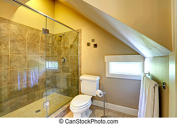 Vaulted ceiling small bathroom with window. View of white toilet and glass door shower