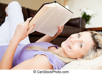 vCharming young woman reading a book lying on the floor