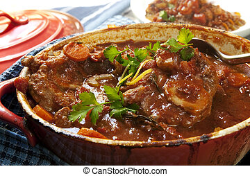 Delicious veal shanks, slow-cooked with vegetables, in a red crock pot. Traditional osso buco.
