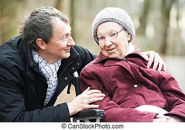 vecchio, donna senior, in, carrozzella, con, attento, figlio