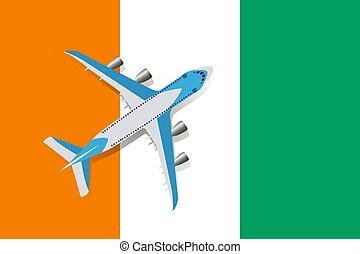 Vector Illustration of a passenger plane flying over the Ivory coast flag.