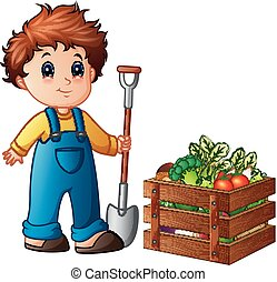 Boy farmer holding shovel with vegetables in a wooden crate