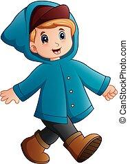 Cartoon boy in blue winter jacket walking - Vector...