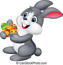 Cartoon bunny holding decorated egg