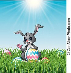 Cartoon bunny waving hand with holding Easter egg in the grass