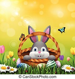 Cute Easter bunny in a basket with colorful eggs on the grass