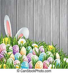 Easter background with bunny ears, flowers and colored decorated eggs in the grass on a wood background