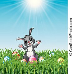 Easter bunny cartoon with Easter eggs in the grass on a background of bright sunshine