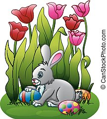 Easter bunny with eggs in the flower garden
