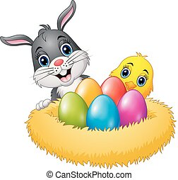 Easter rabbit with chicks and colorful eggs in the nest