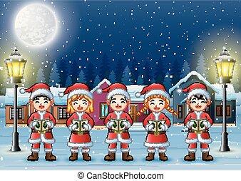 Happy children singing Christmas carols in winter night landscape