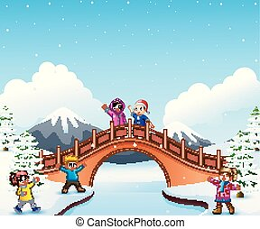 Happy kid on the bridge in the snowing hill
